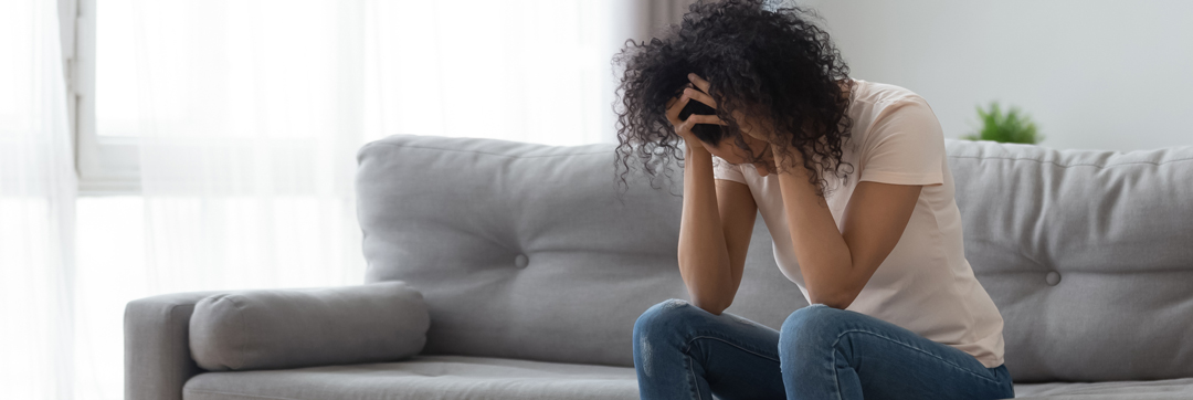 Depressed African American woman holding head in hands, sitting on sofa at home alone, suffering from headache, health problem or thinking about bad relationships problems, break up with boyfriend